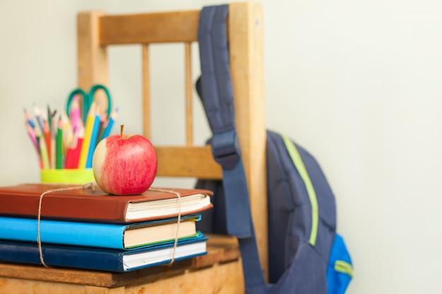 Achtergrond terug naar school met stapel boeken en rode appel.
