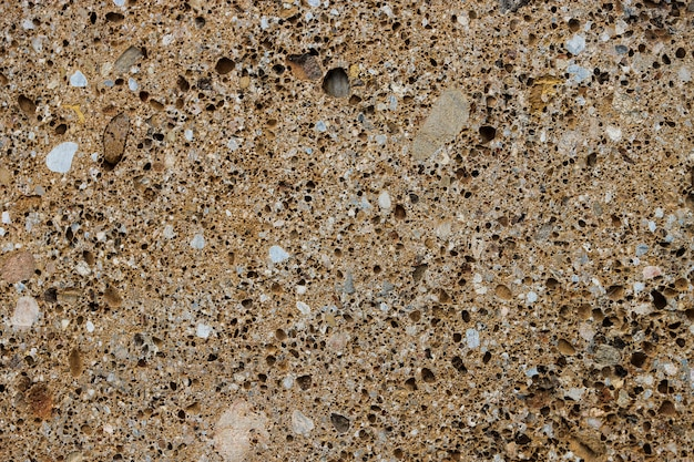 Achtergrond textuur van conglomeraat steen met veel poriën en gaten.