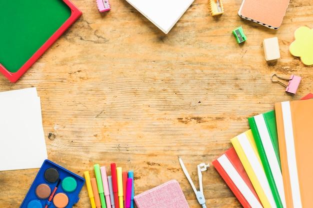 Achtergrond van blocnotes en kleurrijke schoolbenodigdheden