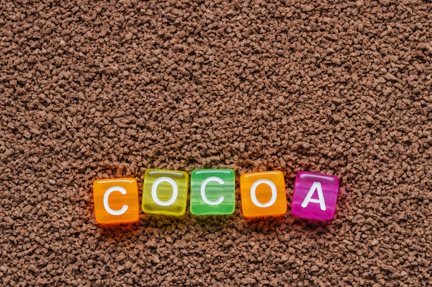 Achtergrond van cacao met de inscriptie van cacao in gekleurde letters op blokjes. close-up, bovenaanzicht
