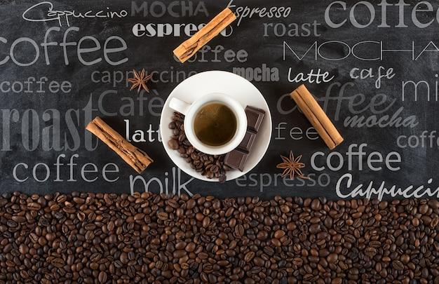 Achtergrond van de bonen van de kopkoffie met kaneel en anijs op zwarte bord met geschreven krijt
