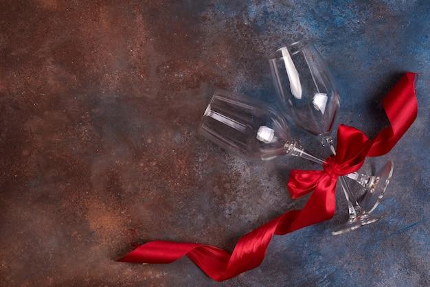 Achtergrond van de viering van de valentijnskaartendag met twee glazen en rood lint