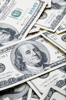 Achtergrond van dollars. noten van honderd amerikaanse dollars zijn verspreid over de achtergrond.