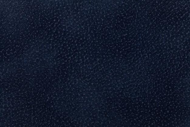 Achtergrond van donkerblauwe die stof met laagdier wordt verfraaid.