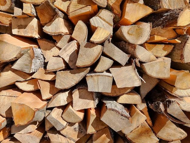 Achtergrond van droge gehakte brandhoutlogboeken die bovenop elkaar in een stapel worden gestapeld. rij van brand houten voorraad voor de winter. selectieve nadruk. brandhout logs