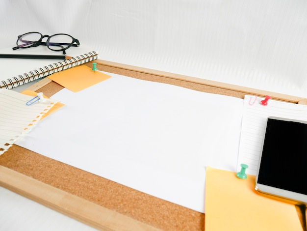 Achtergrond van een houten bord, briefpapier, blanco papier met apparatuur rond, zoals potloden, glazen, geld, mobiele telefoons en kalenders,