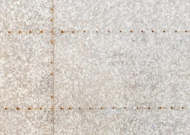Achtergrond van een oude gemarmerde metalen plaat met roestige klinknagels.