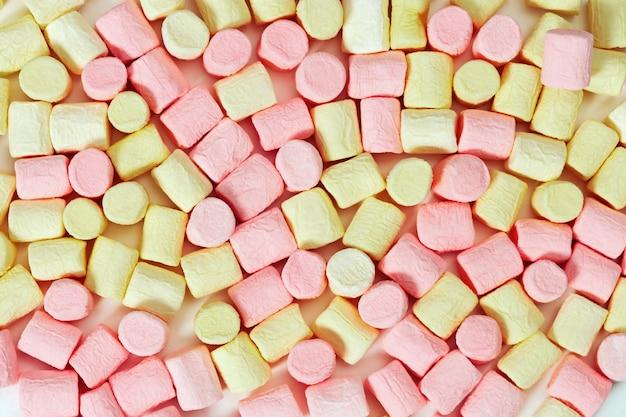 Achtergrond van gele en roze mini marshmallow.