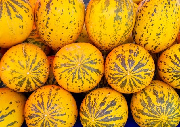 Achtergrond van gele heerlijke turkse meloenen op boerderijmarkt