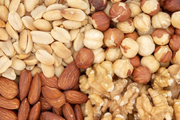 Achtergrond van gemengde noten - hazelnoten, walnoten, amandelen, pijnboompitten