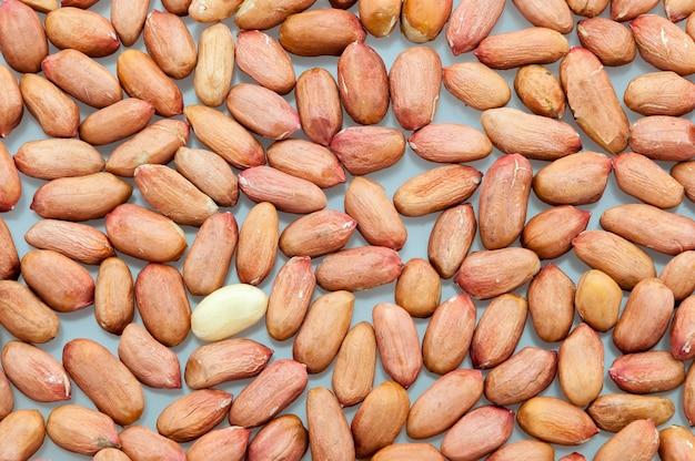 Achtergrond van gepelde pinda's verspreid op een witte tafel close-up