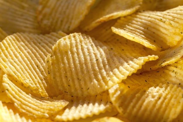 Achtergrond van geribbelde chips met kruiden.