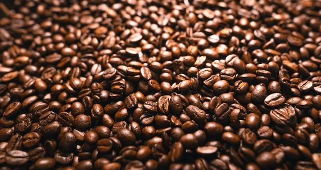 Achtergrond van geroosterde verse bruine koffiebonen, close-up shot van verse koffiebonen-koffietextuur