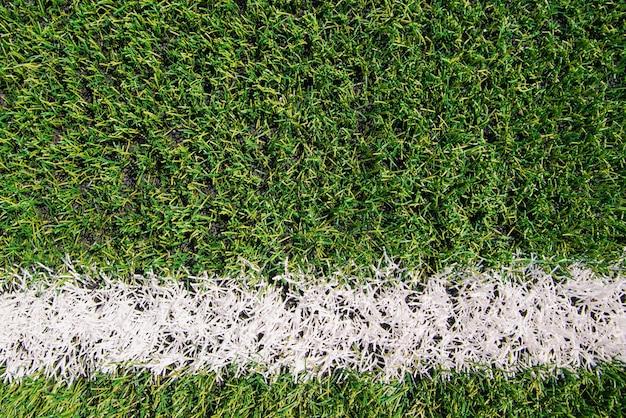 Achtergrond van groen kunstgras. gemarkeerde witte lijnen op het sportveld. textuur met sportthema.