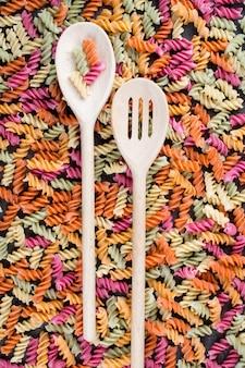 Achtergrond van heldere kleurrijke droge pasta gemaakt van groenten met houten lepels
