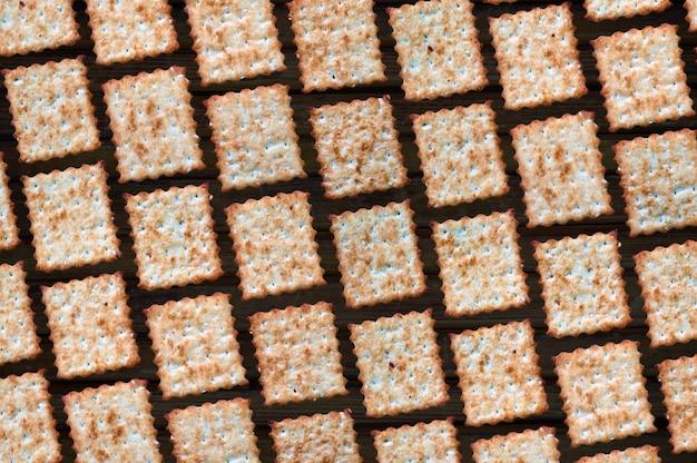 Achtergrond van het rechthoekige vierkant van zoete koekjes close-up op een zwarte achtergrond. veel gefrituurde krokante koekjes in een dambordpatroon