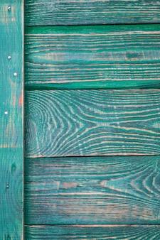 Achtergrond van houten geweven planken met een verticale plank met sporen van groene verf.