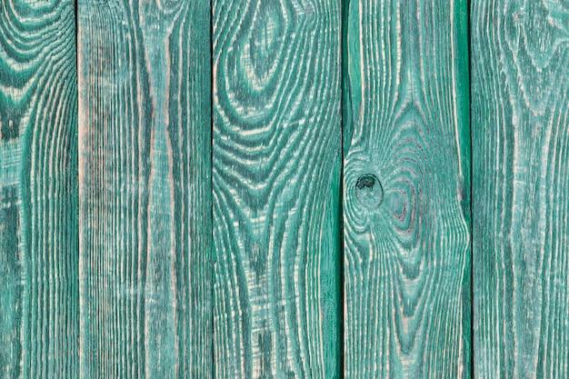 Achtergrond van houten textuurraad met een rest van verf van groene kleur. verticaal.