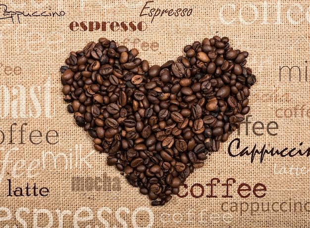 Achtergrond van koffiebonen in de vorm van een hart op juteachtergrond