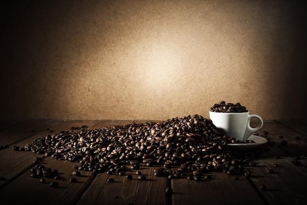 Achtergrond van kopje koffiebonen met jutezak en bailer