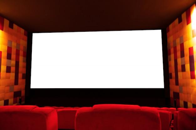 Achtergrond van lege bioskoop of theaterzaal met rode zetel en het lege witte scherm voor reclame.