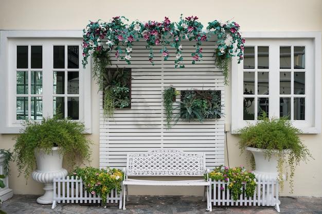 Achtergrond van muur en ramen versieren met sierplanten en lat hout in de achtertuin