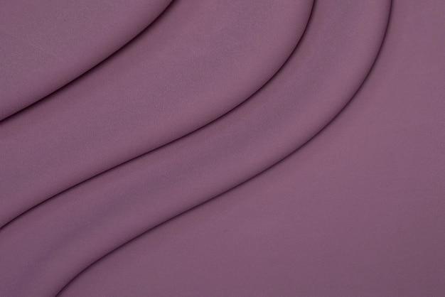 Achtergrond van paarse linnen stof met plooien.