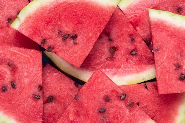 Achtergrond van plakjes sappige rode watermeloen. bovenaanzicht, plat gelegd.