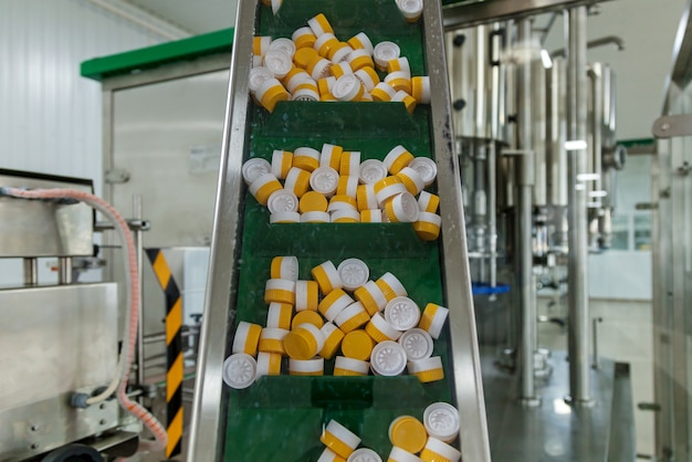 Achtergrond van plastic kroonkurken. plastic doppen voor flessen geel en wit. het productieproces is een lijn voor het verpakken van plastic flessen.