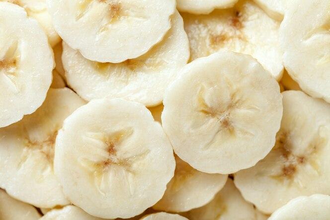 Achtergrond van rijpe gesneden banaanplakken, close-up.