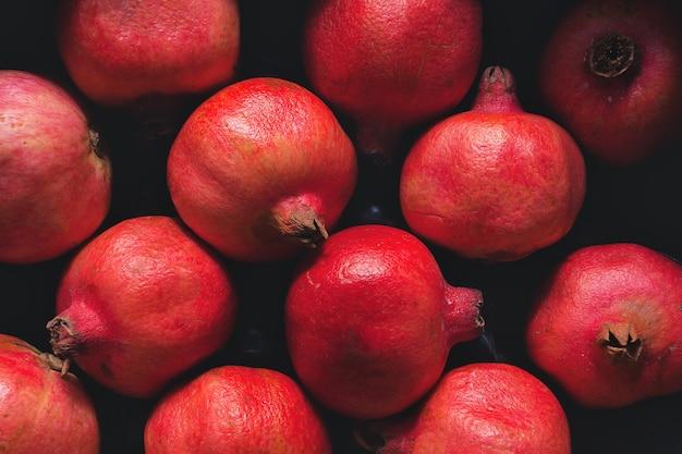 Achtergrond van rijpe granaatappels die op de groentemarkt zijn