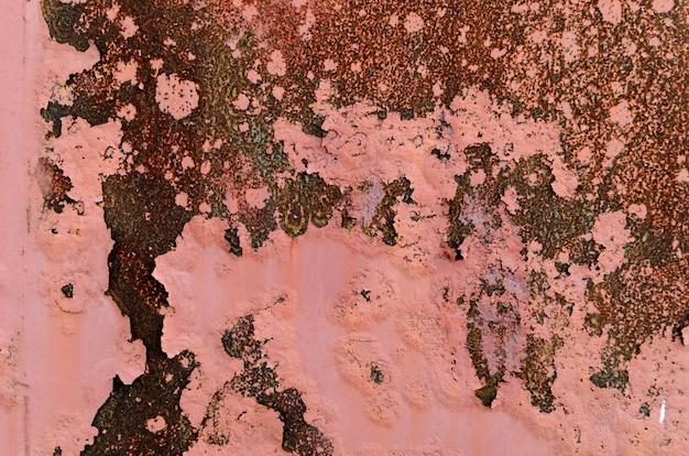 Achtergrond van roestig metaal en roze verf.