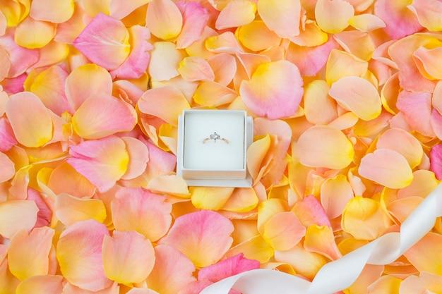 Achtergrond van roze rozenblaadjes, lint en verlovingsring met diamant
