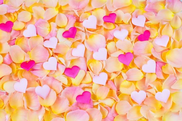 Achtergrond van roze rozenblaadjes veelkleurige harten van satijn
