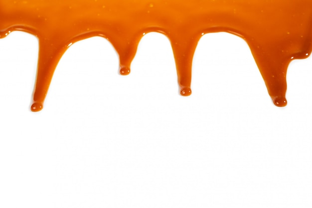 Achtergrond van stromende karamelsaus die op wit wordt geïsoleerd.