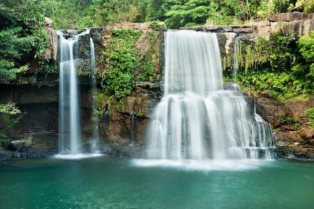 Achtergrond van stromende waterval in nationaal park in diepe boswildernis op berg.