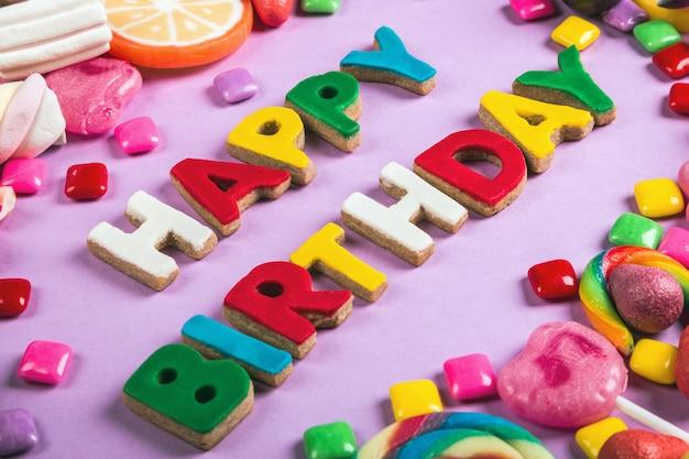 Achtergrond van verschillende zoete, lollies, kauwgom, snoepjes, marshmallows en de woorden verjaardag. verjaardagswensen