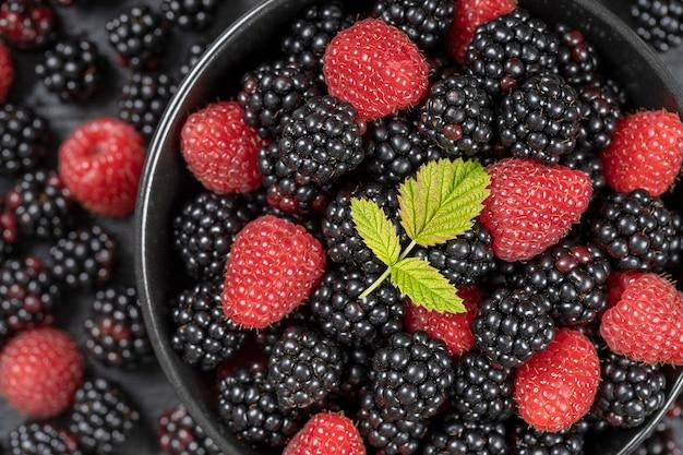 Achtergrond van verse biologische bramen en frambozen, close-up. veel rijpe sappige wilde vruchten rauwe bessen in een zwarte plaat. bovenaanzicht bramen en frambozen