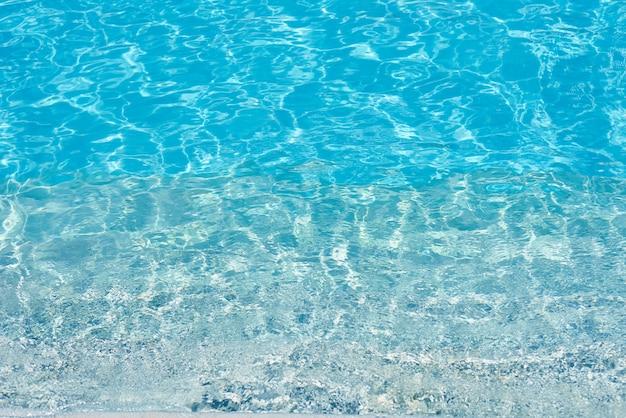 Achtergrond van water in blauw zwembad, waterspiegel met een zonbezinning