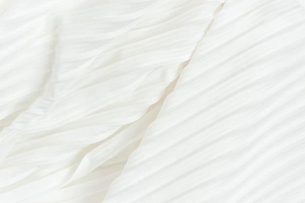 Achtergrond van witte geplooide stof diagonaal gelegen. plissé doek textuur van witte vrouwelijke rok close-up.