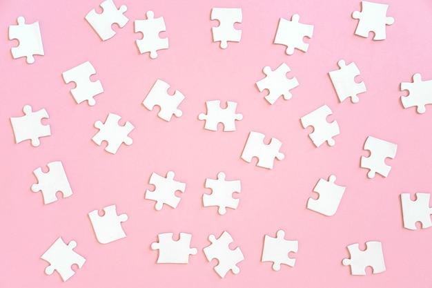 Achtergrond van witte puzzelstukjes op roze, bovenaanzicht