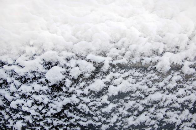 Achtergrond van witte sneeuwvlokken op zwart glas, close-up