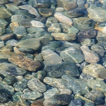 Achtergrond van zee gekleurde stenen onder water.