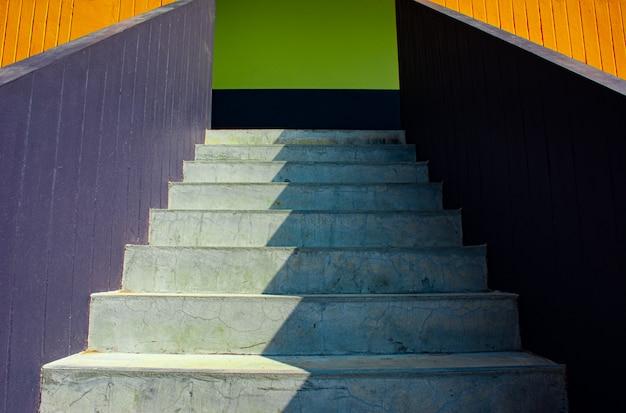 Achtergrond van zonlicht en schaduw op de witte oppervlakte van steenstappen van kleurrijke trap in lage hoek en perspectiefmening, beeld voor het ontwerpconcept van de huisbuitendecoratie.