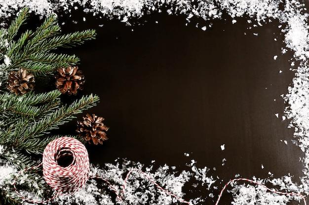 Achtergrond voor kerstgroeten met boomtakken, kegels en sneeuw