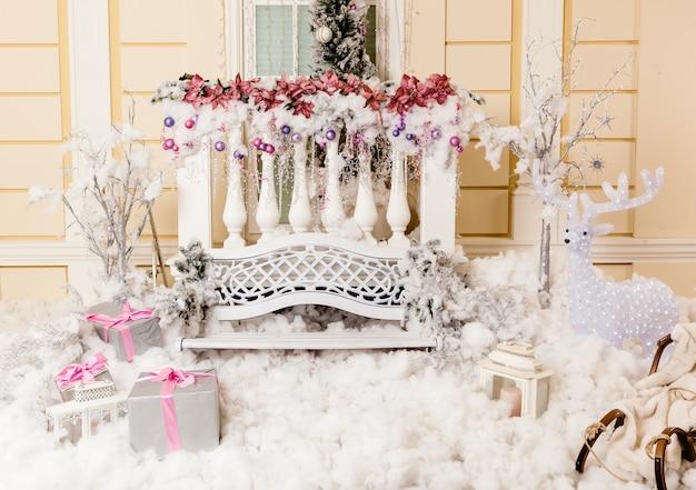 Achtergrond voor kerstverhalen, kerstcompositie met cadeautjes, rendieren, slee, bank en kaarsen voor de kerstbijeenkomst