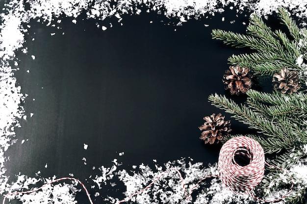 Achtergrond voor nieuwe jaargroeten met boomtakken, kegels en sneeuw