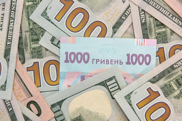 Achtergrond voor ontwerpbankbiljetten van amerikaanse dollars en oekraïense hryvnia. wisselkantoor
