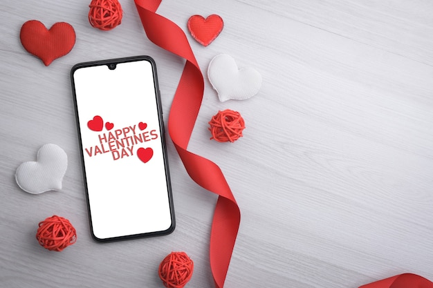 Achtergrond voor valentijnsdag wenskaart. valentijnsdag concept. rode geschenk linten, geschenken, harten op een houten achtergrond. bovenaanzicht. mobiele telefoon, smartphone.