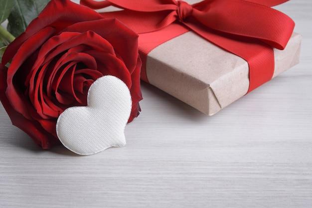 Achtergrond voor valentijnsdag wenskaart. valentijnsdag concept. rode geschenk linten, geschenken, harten op een houten achtergrond.